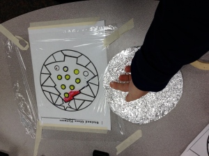 Carefully slide the file folder that you wrapped with aluminum foil under the finished picture.